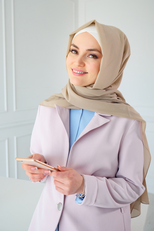 Portrait of muslim business woman in beige hijab with mobile phone in office, close-up Stockfoto