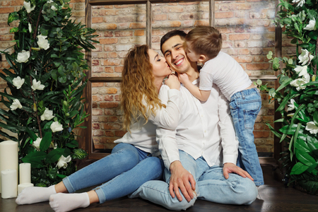 woman and child kissing man. happy family in casual clothes