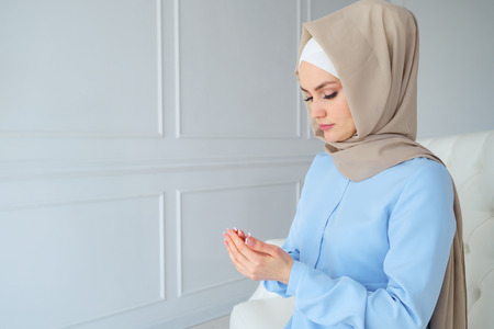 young muslim woman in beige hijab and traditional clothes praying for Allah, muslim God. copy space.