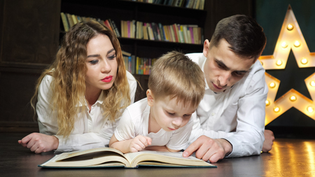 Happy young family mom, son and dad are reading a book together laying on the floor at home in living room after working day. Family reading tradition.