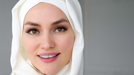 Portrait closeup face of beautiful muslim woman wearing white hijab is looking at camera and smiling on white background, copy space Stock Photo