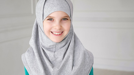 Portrait of young attractive muslim 9-years girl wearing grey hijab and traditional dress is rising her eyes, looking at the camera and smiling on light background. copy space