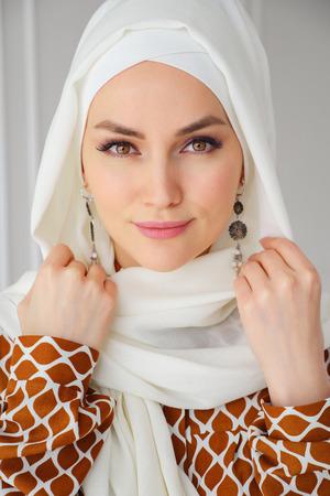 Ritratto di bella giovane donna araba musulmana che indossa l'hijab bianco che guarda l'obbiettivo, primo piano