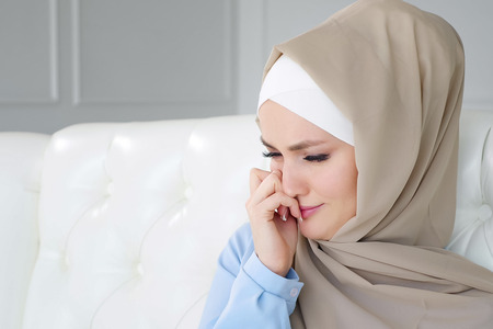 Portrait of beautiful young sad crying muslim woman in beige hijab is sitting on the sofa at home. She cries and wipes her tears with her hands, copy space Imagens
