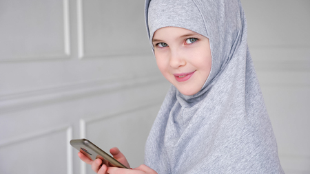 Portrait of young muslim teen girl in grey hijab is playing smartphone, shyly looking at camera and smiling in light interior, side view. copy space Archivio Fotografico