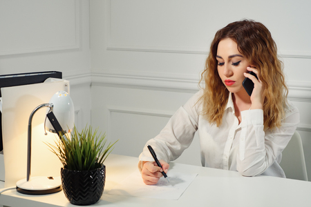 Young curly-haired woman secretary is talking on mobile phone with client and taking notes sitting at table in the office. Office working concept.