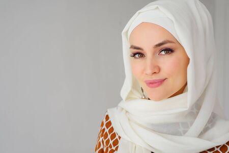 Ritratto di bella giovane donna araba musulmana che indossa l'hijab bianco che guarda l'obbiettivo, copia spazio