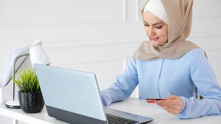 Online shopping concept. Portrait of muslim young woman in beige hijab and traditional blue dress is buying online with a credit card and laptop. Stock Photo