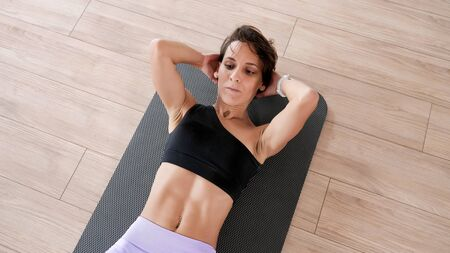 Athletic woman in sportswear is pumping the abdominals. She is doing abs exercise on mat in gym. Sport and fitness concept.