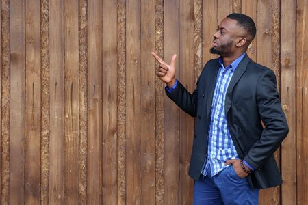 African black man with beard pointing away side with finger on wood background. He is serious and looks away, copyspace Reklamní fotografie