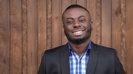 Retrato de joven barbudo negro. Hombre afroamericano en traje está sonriendo y mirando a cámara sobre fondo de madera oscura. Está feliz y confiado.