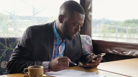 Black guy is making paperwork. american businessman is filling documents in summer tent cafe looking in smartphone. Writing papers. Hot cup of coffee on the table. He wears shirt and suit jacket. Stock Photo