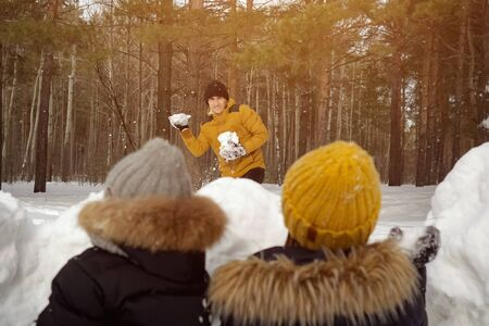 Man is playing snowballs with his family in winter park, sunlight. His wife and little son are hiding before snow wall. They are sitting back to camera.
