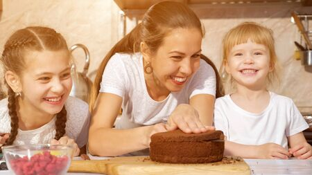 Family portrait of mom and daughters are preparing birthday cake together, mom is cutting sponge cake using knife in kitchen. Standard-Bild