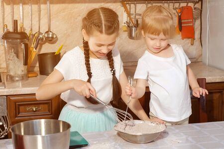 Girls sisters are mixing ingredients using beater in a bowl in kitchen at home, the younger sister tries all tastes.