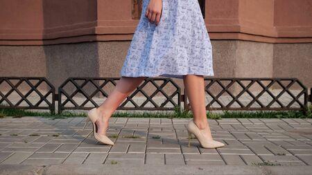 lady in blue dress gorgeous legs in beige high heels walk along street tiled sidewalk on warm day close low angle shot 写真素材