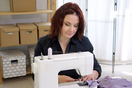 Dressmaker sewing clothes. Fashion designer sewing new model of clothes. Seamstress woman works on sewing machine in tailoring workshop business. She stitches details for future clothing.