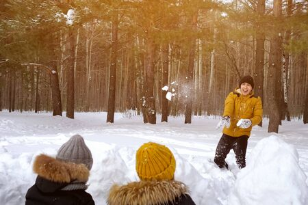 Family is playing snowball fight. Mom and little son are hiding behind snow wall and throwing snowballs to dad. Family weekend in winter park, sunlight