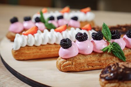 Traditional French dessert. Eclair with cream, strawberries, cherry, mint on wooden background selective focus