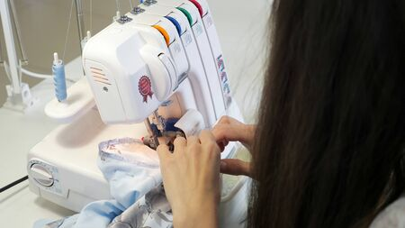 Finish detail with serger overlock stitch. Seamstress brunette woman sewing in workshop atelier on overlock cloth edges, hands closeup. Processing tissue overlock. Tailoring business in factory.