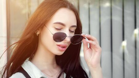 pretty brunette with long loose flowing hair waved by wind and plump lips poses taking off black sunglasses copy space