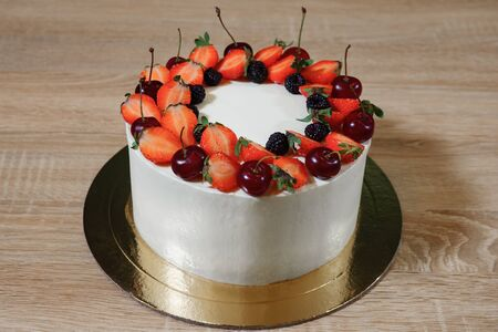 beautiful cake with strawberries, cherry, blackberry and cream on the wooden background.