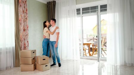 happy couple wearing jeans standing in new house near big boxes and looking at each other 写真素材