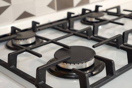 Cerca de la moderna estufa de gas plateada de acero inoxidable con elementos negros