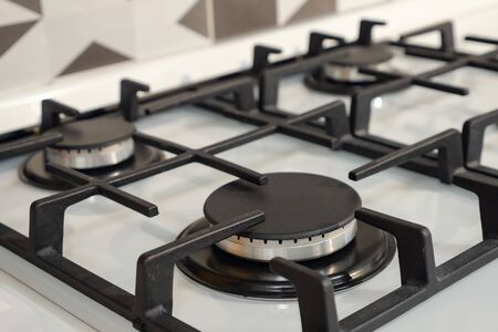 close up of modern stainless steel silver gas stove with black elements