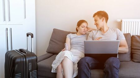 Young couple is booking transfer to the airport on laptop sitting on sofa at home. They are going on vacation with passports and suitcase. Choosing and booking tour and hotel.