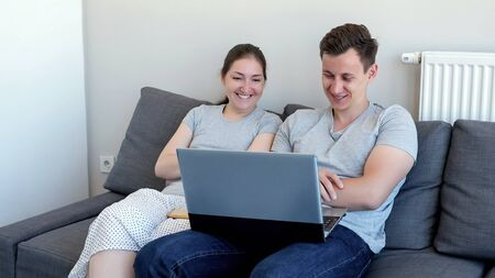 Young couple, man and woman are watching comedy movie on laptop and laughing sitting on sofa. They are in their modern apartment.