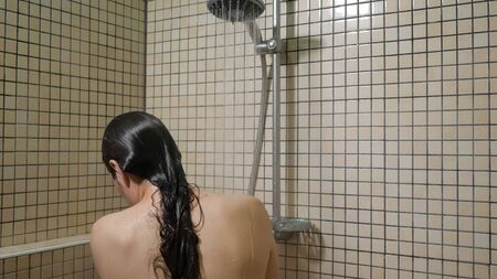 Brunette woman with long hairs is taking a shower with rainwater showerhead, back view. She is washing her body standing under the water.