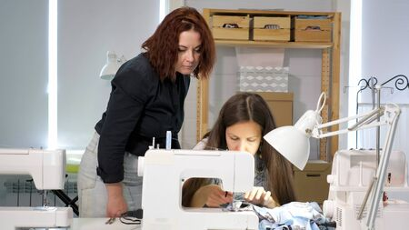 Dressmaker teaches new employee to work in workshop. Cutting and sewing courses. Seamstress teacher controls looks how student sew on sewing machine in workshop. Traineeship concept. Probation period.