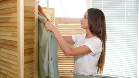 gorgeous fair haired lady takes trendy jacket from wooden hanger puts on by folding screen in fashion shop posing close