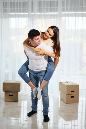 Happy couple have fun in their new apartment. woman hugs man and looking each other