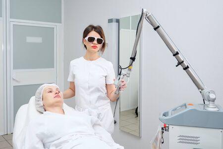 Une travailleuse de salon de beauté procède à l'épilation à l'aide d'un appareil de dernière génération équipé d'un système de refroidissement Banque d'images