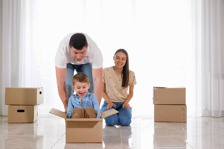 father rides happy small son wearing blue shirt in big cardboard box near beautiful mother sitting in floor