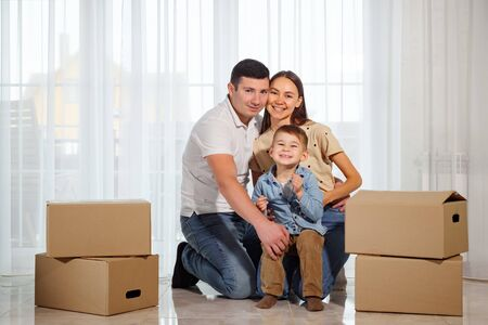 Happy family sitting on the floor in their new house among cardboard boxes.