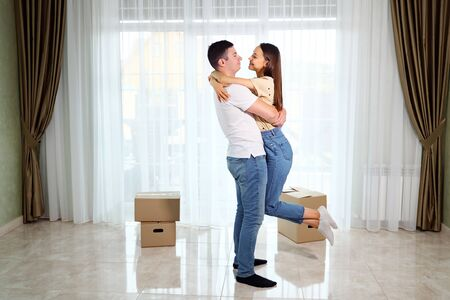 happy couple carries boxes with belongings into new house with beautiful interior hugs and kisses in lounge