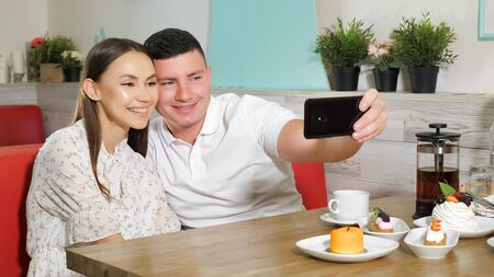 happy young couple girl guy makes selfie on modern smartphone sitting at served with cakes and drinks table in cafe