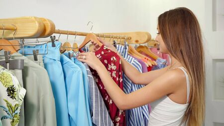 pretty fair haired lady holds hanger with gorgeous red dress and tries on by rack in clothes shop close view Stockfoto