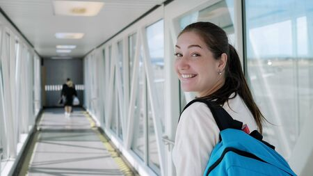 Happy young woman with backpack is going on telescopic gangway to the airplane. She turns around, looks at the camera and smiles.