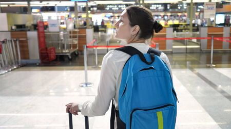 Young woman traveller with backpack and suitcase in airport terminal building. She is standing and looking around, back view.