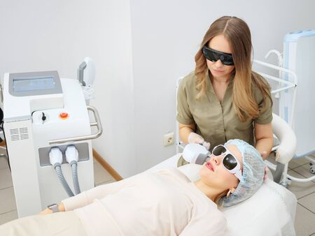 cosmetological clinic worker performs radical hair removal on girl patient face using improved special device Reklamní fotografie