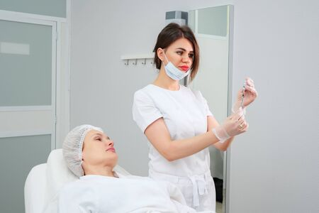 cosmetologist in mask holds syringe filled with biocompatible medication to carry out medical skin therapy