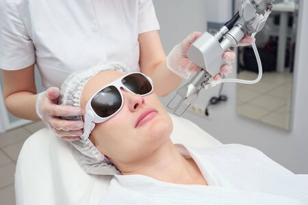 cosmetologist hand holds neodymium laser at patient face in glasses doing cosmetological procedure selective focus