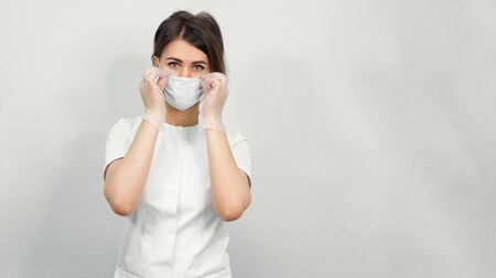 beautiful woman beautician puts on white protection mask standing against medical center wall copy space