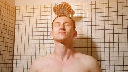 Portrait of handsome man taking a shower with rainwater showerhead in the morning. He is combing his hairs with hands standing under the water, close-up
