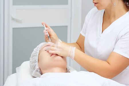 cosmetologist carries out medical procedure with collagen filler to smooth wrinkles on woman forehead Reklamní fotografie