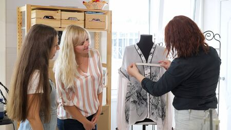 Cutting and sewing courses. Dressmaker explains to two women how to take measurements for tailoring in workshop. She measures the mannequin using tape measure. Business tailoring handmade clothes. 写真素材